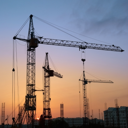construct site: Industrial landscape with silhouettes of cranes on the sunset background