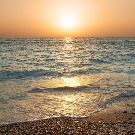 Sonnenuntergang über dem Meer Big Sonne und Wellen am Strand Lizenzfreie Bilder