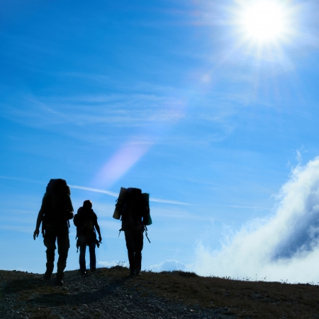 Silhouette of hiking friends against sun and blue sky Stock Photo - 16825443