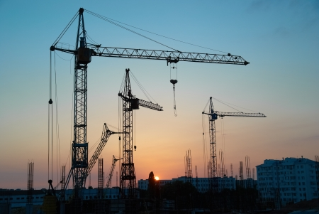 site: Industrial landscape with silhouettes of cranes on the sunset background