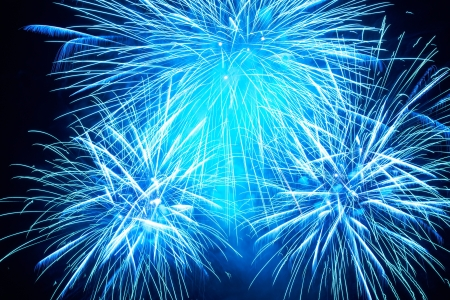 christmas in july: Blue colorful fireworks on the black sky background Stock Photo