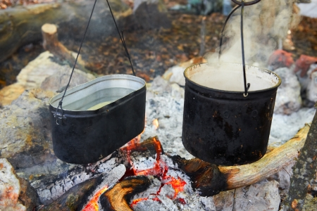 Boiling water in two pots above the fire. Stock Photo - 17452398