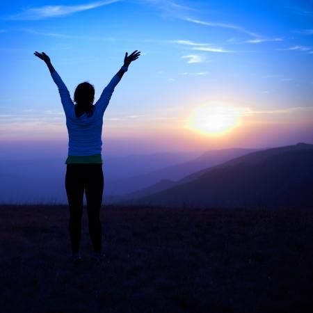 Silhouet van jonge vrouw tegen zonsondergang met blauwe hemel Stockfoto - 17416941
