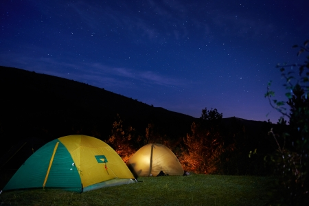 silent night: Illuminated yellow camping tent under stars at night Stock Photo