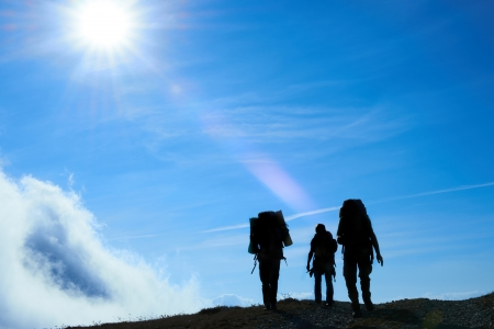 Silhouette of hiking friends against sun and blue sky photo
