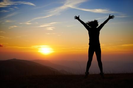 Silhouette der jungen Frau springt gegen Sonnenuntergang mit blauem Himmel