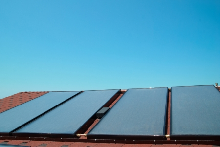 Solar water heating panels on the red roof. Gelio system photo