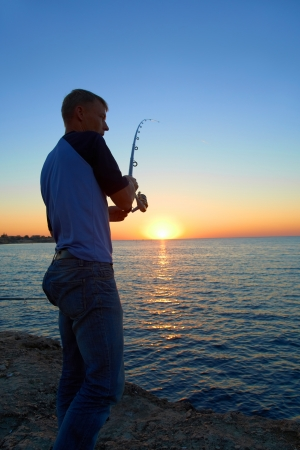 Fisherman fishes on the lake. Silhouette at sunset Stock Photo - 17662538