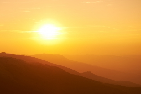 Beautiful sunset at the mountains. Colorful landscape with sun and orange sky Reklamní fotografie