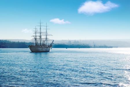 Beautiful sailing vessel in the sea comes into bay photo
