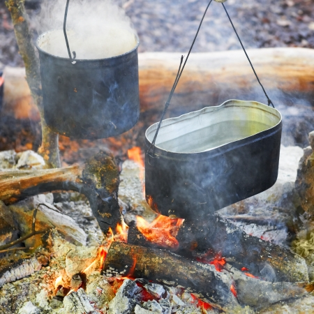 Boiling water in two pots above the fire. photo