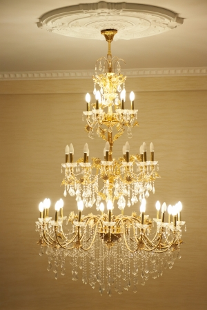 Beautiful crystal ancient chandelier in a hall. Lamp with soft yellow light photo