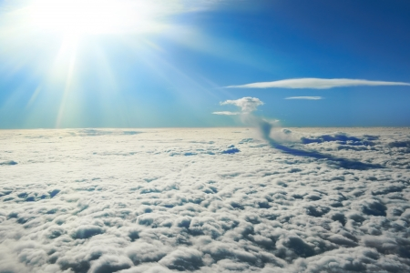 Blue sky, sun and clouds. Plane view above the earth, can be used for background