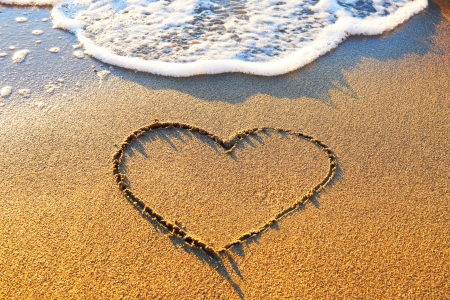 Heart drawn on the beach sand with sea foam and wave  photo