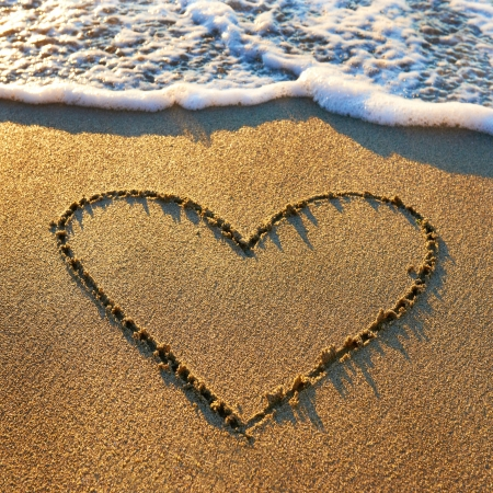 Heart drawn on the beach sand with sea foam and wave Stock Photo - 18600197