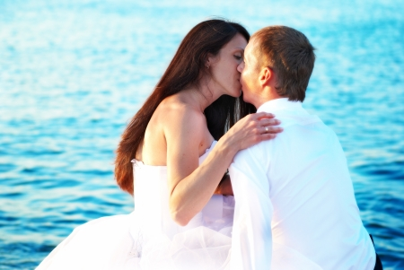 Beautiful wedding couple- bride and groom kissing at the beach. Just married photo