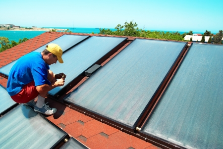 gelio: Worker mounting solar water heating panels on the roof.