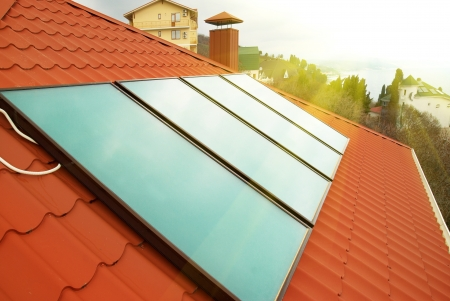 collectors: Solar water heating system (geliosystem) on the red house roof.