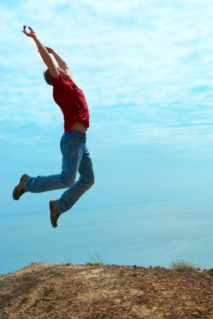 Man jumping cliff against sea and mountain with blue sky photo