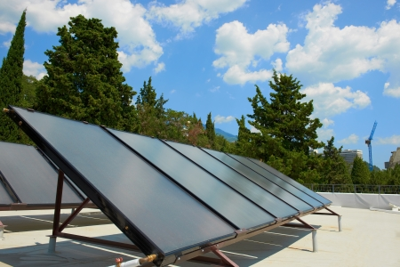 solar panel house: Solar water heating system on the red roof  Gelio panels  Stock Photo