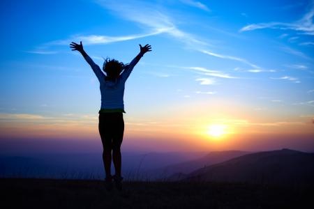 Silhouette der jungen Frau springt gegen Sonnenuntergang Lizenzfreie Bilder