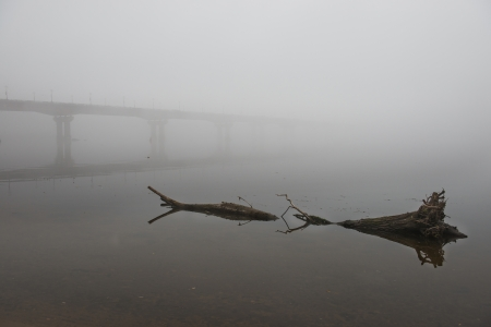 old pier: Bridge through Dnepr river in misty morning with a big log Stock Photo
