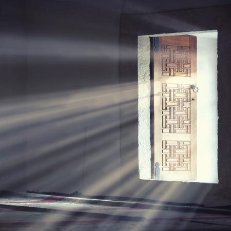 Light entering through open door to a dark empty room   photo