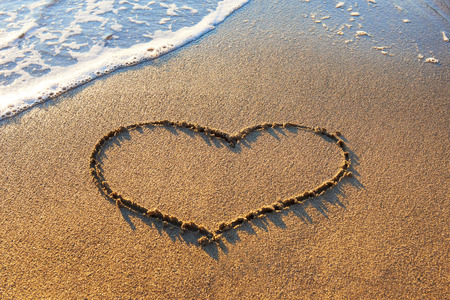 heart in sand: Heart drawn on the beach sand with sea foam and wave  Stock Photo
