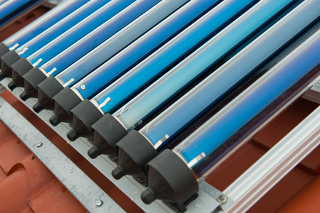voltaic: Vacuum collectors- solar water heating system on red roof of the house