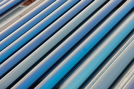 Vacuum collectors- solar water heating system on red roof of the house  photo