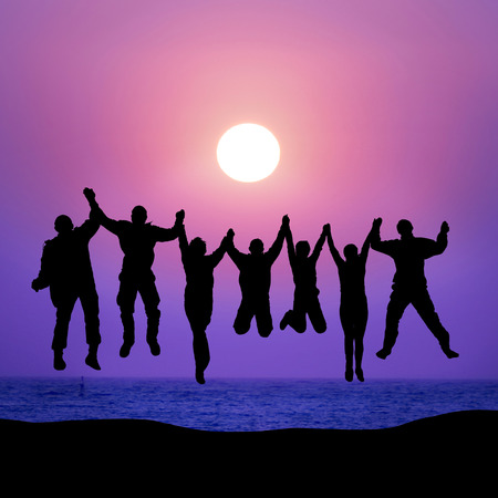 Group of friends jumping against sunset above the sea 스톡 콘텐츠