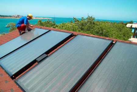 Worker solar water heating panels on the roof  photo