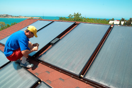 gelio: Worker solar water heating panels on the roof