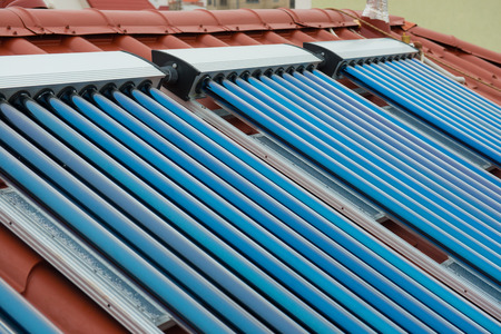 gelio: Vacuum collectors- solar water heating system on red roof of the house