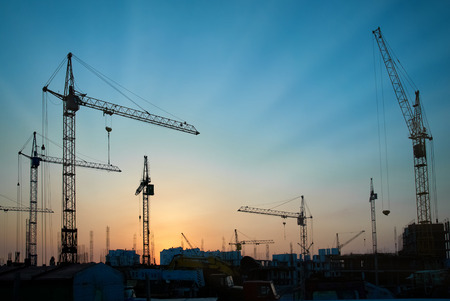Industrial landscape with silhouettes of cranes on the sunset background photo