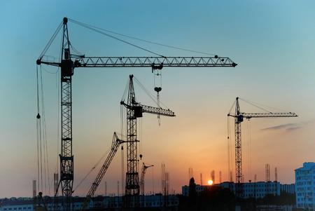 Industrieel landschap met silhouetten van kranen op de zonsondergang op de achtergrond Stockfoto