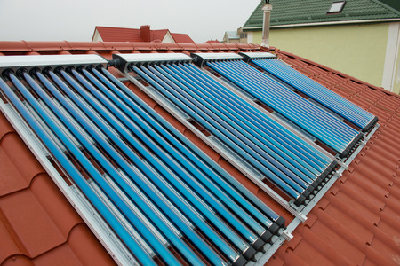gelio: Vacuum collectors- solar water heating system on red roof of the house.