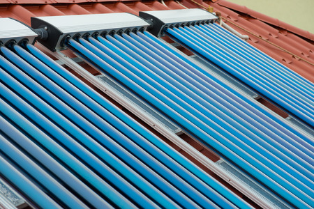 tube station: Vacuum collectors- solar water heating system on red roof of the house.
