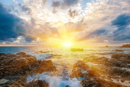 Zonsondergang op het strand met golven, zee, rotsen en dramatische hemel. Landschap met zon in het midden Stockfoto