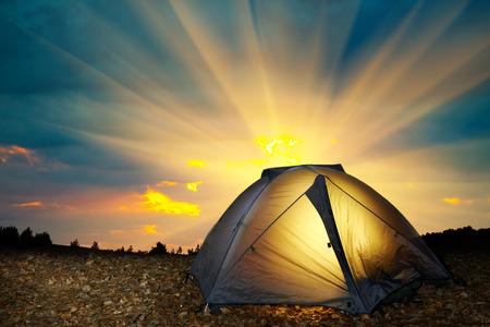 Illuminated yellow camping tent under stars at night.