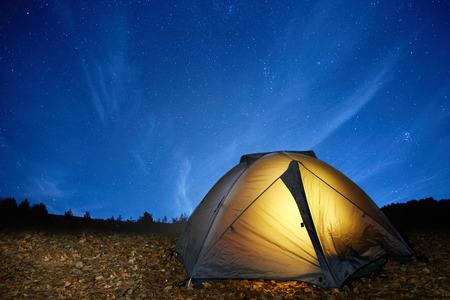 campamento: Tienda de campaña para acampar iluminada amarillo bajo las estrellas en la noche
