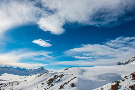 montañas nevadas: Montañas azules nevadas en las nubes. Estación de esquí de invierno