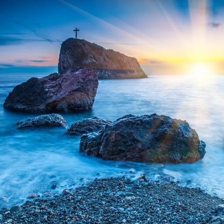 cruz roja: Puesta de sol en la playa con el mar, las rocas y el cielo dram�tico