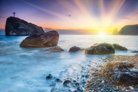 Red Cross: Puesta de sol en la playa con el mar, las rocas y el cielo dram�tico. paisaje de la playa