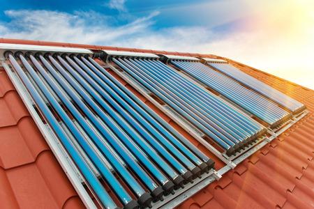 Vacío collectors- sistema de calentamiento solar de agua en el techo rojo de la casa.
