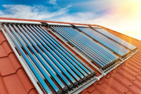 solar roof: Vacuum collectors- solar water heating system on red roof of the house.