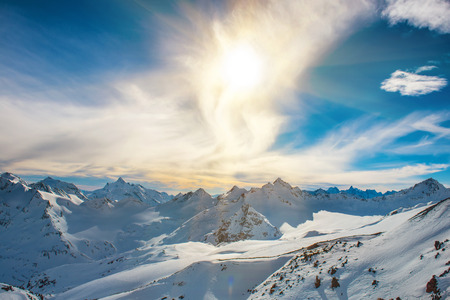 elbrus: Snowy blue mountains in clouds. Winter ski resort