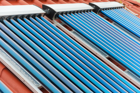 Vacuum collectors- solar water heating system on red roof of the house. photo