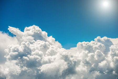 above the clouds: Blue clouds, bright sun and sky. Natural background Stock Photo