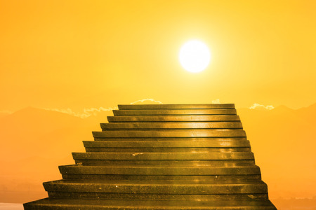 Stairway to heaven. Stairs towards sun on the orange sunset with clouds photo